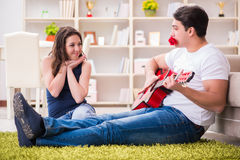 The romantic pair playing guitar on floor Stock Image