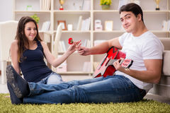 The romantic pair playing guitar on floor Royalty Free Stock Image
