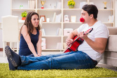 The romantic pair playing guitar on floor Royalty Free Stock Images