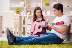 The romantic pair playing guitar on floor Royalty Free Stock Photo