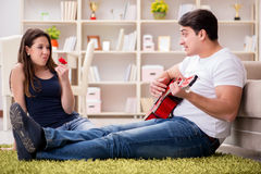 The romantic pair playing guitar on floor Stock Photography
