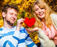 Romantic pair sit on bench in autumnal park. Expressing feelings and affection. Confess love with romantic gesture. Young couple sit on bench in park holding Stock Photography
