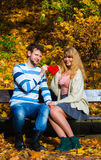 Romantic pair sit on bench in autumnal park. Expressing feelings and affection. Confess love with romantic gesture. Young couple sit on bench in park holding Stock Image
