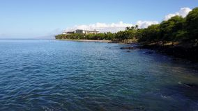 Romantic panorama of the waters of ocean near shore on the background of blue sky and luxurious resort hyatt on island. Fashionable resort hyatt on island maui stock video footage
