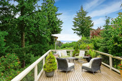 Romantic patio area on walkout deck with bay view. Wicker patio set with heater royalty free stock photography