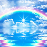 Romantic and peaceful seascape scene with rainbow on cloudy blue sky Royalty Free Stock Image