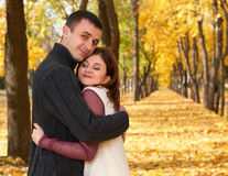 Romantic people, happy adult couple embrace in autumn city park, trees with yellow leaves, bright sun and happy emotions, tenderne Stock Photos