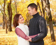 Romantic people, happy adult couple embrace in autumn city park, trees with yellow leaves, bright sun and happy emotions, tenderne Stock Image