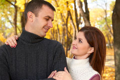 Romantic people, happy adult couple embrace in autumn city park, trees with yellow leaves, bright sun and happy emotions, tenderne Royalty Free Stock Images