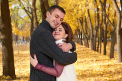 Romantic people, happy adult couple embrace in autumn city park, trees with yellow leaves, bright sun and happy emotions, tenderne Royalty Free Stock Photos