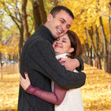 Romantic people, happy adult couple embrace in autumn city park, trees with yellow leaves, bright sun and happy emotions, tenderne Royalty Free Stock Image