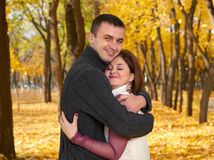 Romantic people, happy adult couple embrace in autumn city park, trees with yellow leaves, bright sun and happy emotions, tenderne Royalty Free Stock Photography