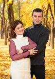 Romantic people, happy adult couple embrace in autumn city park, trees with yellow leaves, bright sun and happy emotions, tenderne Stock Photo