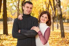 Romantic people, happy adult couple embrace in autumn city park, trees with yellow leaves, bright sun and happy emotions, tenderne Stock Photography