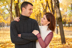 Romantic people, happy adult couple embrace in autumn city park, trees with yellow leaves, bright sun and happy emotions, tenderne Royalty Free Stock Photo