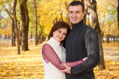 Romantic people, happy adult couple embrace in autumn city park, trees with yellow leaves, bright sun and happy emotions, tenderne Stock Images