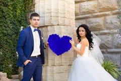 Romantic photo of beautiful couple on white background. The couple holding heart decoration Stock Image