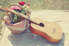 Romantic photo guitar, basket with wine, bouquet flowers on plaid. Romance, love, date, Valentines day Stock Photo
