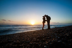 Romantic photo of kissing couple during sunset. Made in Brighton, England Royalty Free Stock Images