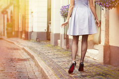 Romantic photo of woman walking in old town. In early morning Stock Image