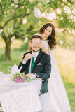 Romantic picknick in park. Playful bride shutting eyes of her lovely new husband Stock Photography