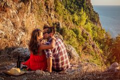 Romantic picnic of loving couple with seaside and mountain view at sunset Stock Photos
