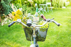 Romantic picnic - flowers and wine in bicycle basket. Summer outdoor romantic picnic in the garden. Bicycle basket filled with wild-flower bunch (bouquet), white Royalty Free Stock Photos