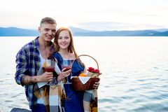Romantic picnic by the lake. Couple is having a romantic picnic by the lake Stock Image
