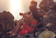 Romantic picnic of loving couple with seaside and mountain view at sunset Stock Image