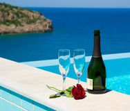 Romantic picnic near pool in mediterranean resort. Romantic picnic near infinity pool in luxury mediterranean resort. Shampagne and rose. Greece Stock Image