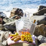 Rest by the sea with grapes, apples, pears, baguettes, wine and a basket on the coverlet Royalty Free Stock Images
