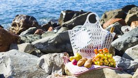 Rest by the sea with grapes, apples, pears, baguettes, wine and a basket on the coverlet Stock Photography