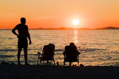 Romantic picnic by the sea. Couple relaxing on the beach while watching the sunset. Romantic evening by the sea. Family vacation Royalty Free Stock Images