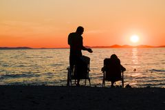 Romantic picnic by the sea. Couple relaxing on the beach while watching the sunset. Romantic evening by the sea. Family vacation stock photo