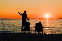 Romantic picnic by the sea. Couple relaxing on the beach while watching the sunset. Romantic evening by the sea. Family vacation Royalty Free Stock Photos
