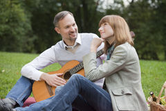 Romantic Picnic With Man Playing Guitar Royalty Free Stock Images