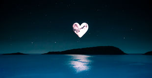 Romantic picture of a heart-shaped moon over a calm sea. Sky with heart shaped moon and lots of stars over a calm sea in the middle of the night Stock Image