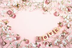 Romantic pink background with small flowers and wooden alphabet. Place for text. Flat lay, top view royalty free stock photo