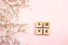 Romantic pink background with small flowers and wooden alphabet. Place for text. Flat lay, top view royalty free stock image