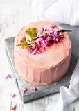 Romantic Pink cake decorated by flowers, rustic style for weddings, birthdays and events, mothers day on light background with royalty free stock image