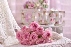 Romantic pink rose bouquet lying on the bed. In shabby chic style interior Stock Photos