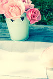 Romantic pink roses in a vase and white paper with copy space Royalty Free Stock Photos