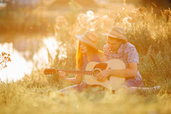 Romantic place in field, when happy couple sitting on grass smiling and singing. Wife and husband looking each other and playing o Royalty Free Stock Image