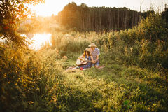 Romantic place in field, when happy couple sitting on grass smiling and singing. Wife and husband looking each other and playing o Royalty Free Stock Photography