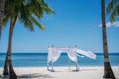 Romantic place by the sea. White fabric curtains fluttering in the wind. Beach shade with white gracefully fluttering fabric curtains on seashore. Sea breeze royalty free stock photography