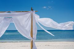 Romantic place by the sea. White fabric curtains fluttering in the wind. Beach shade with white gracefully fluttering fabric curtains on seashore. Sea breeze stock photo