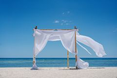 Romantic place by the sea. White fabric curtains fluttering in the wind. Beach shade with white gracefully fluttering fabric curtains on seashore. Sea breeze royalty free stock photos