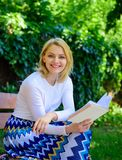 Romantic poem. Enjoy rhyme. Woman happy smiling blonde take break relaxing in garden reading poetry. Girl sit bench. Relaxing with book, green nature background stock images