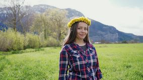 Romantic portrait of a beautiful girl with dandelions wreath. Beautiful girl stands on a background of mountains. 4k stock footage