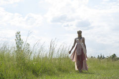 Romantic portrait of bohemian blonde in field of grass. Color portrait of a beautiful blonde girl wearing romantic bohemian dress, hairstyle and necklace Royalty Free Stock Photos